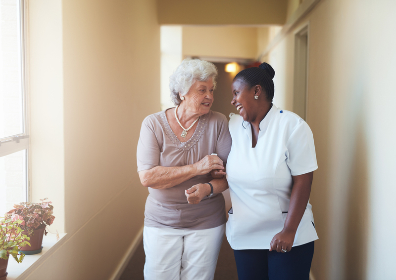 A woman in an assisted living home with a caretaker.
