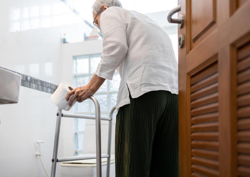 Male senior enters bathroom at a Las Vegas senior assisted living facility.