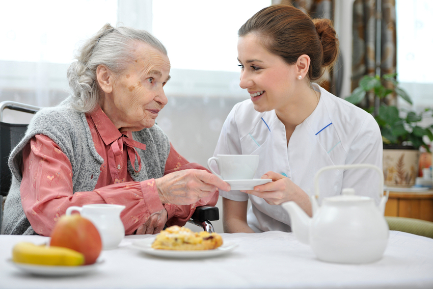 A woman in a skilled nursing home being helped by a nurse.