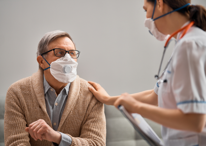 A man speaking to a doctor with a mask on.