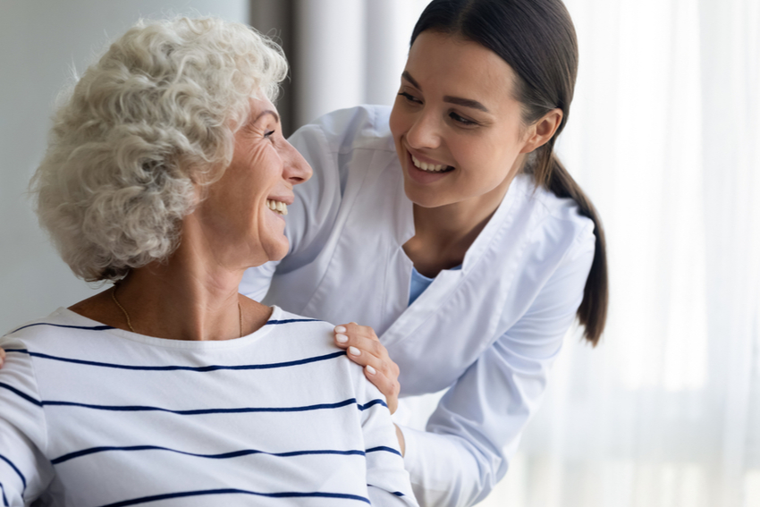 A woman helping a senior at a skilled nursing home.