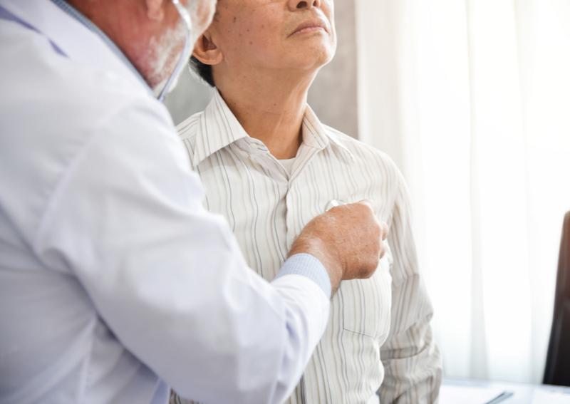 A doctor checks a senior for pneumonia