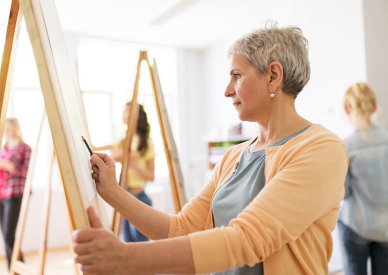 A senior woman painting.