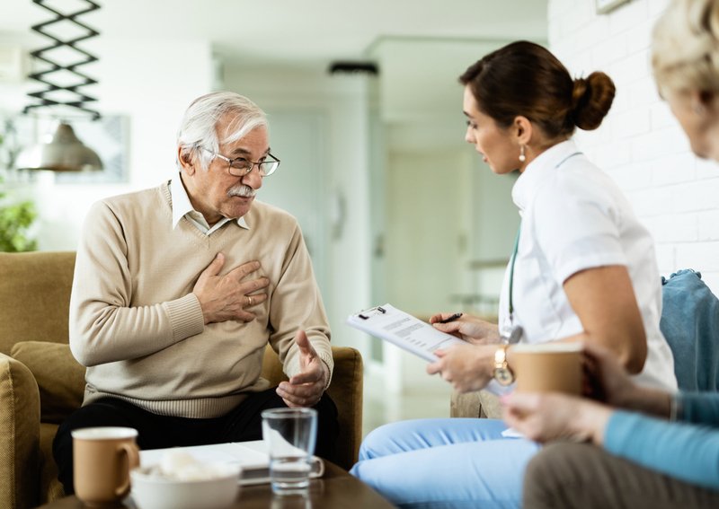A man and a nurse discussing signs of strokes.