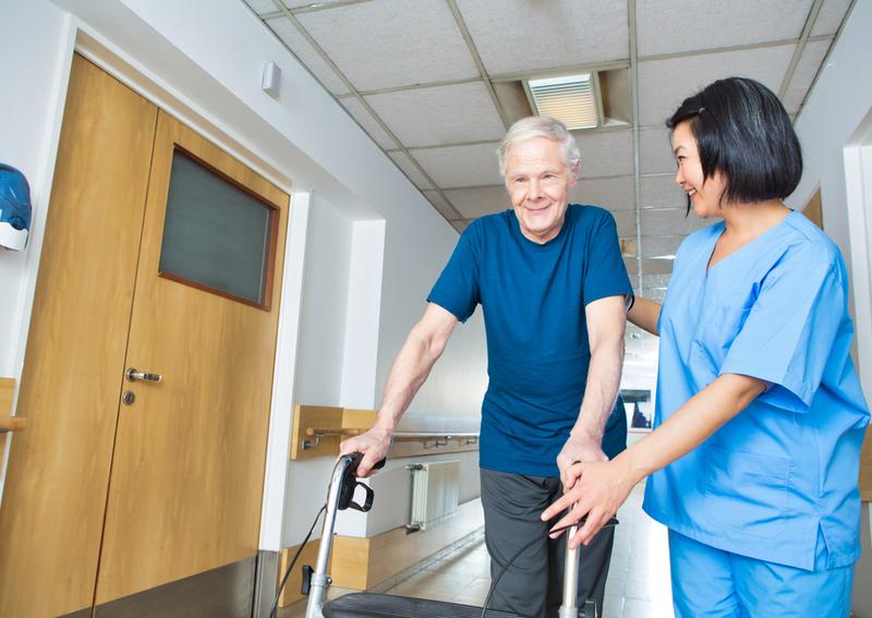 A nurse helps a man with a walker.